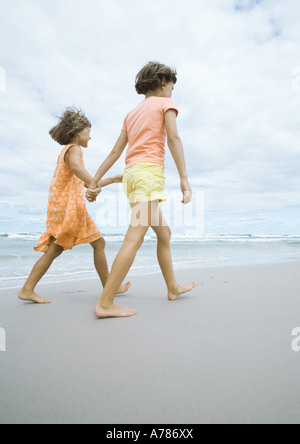 Two girls walking, holding hands, on beach - Stockfoto