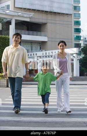 Family crossing crosswalk, holding hands - Stockfoto