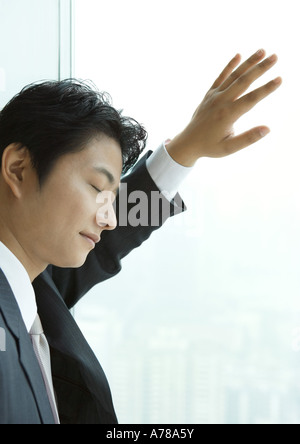 Businessman leaning against window of high rise, eyes shut - Stock Photo