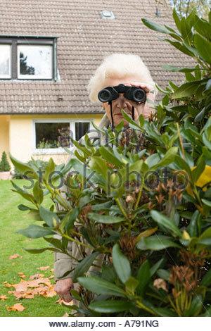 Senior woman spying - Stock Photo