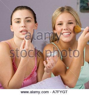 Two teenage girls applying make up - Stock Photo