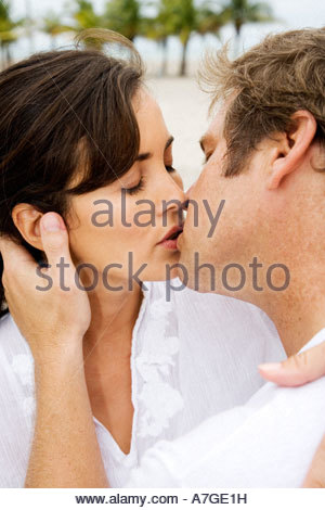 A couple kissing on a beach - Stock Photo