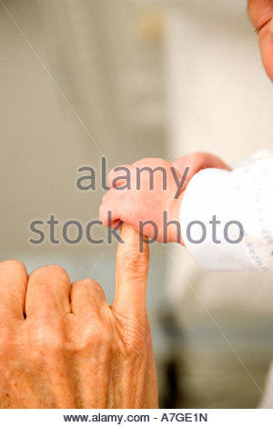 A baby's hand holding their grandparent's finger - Stockfoto