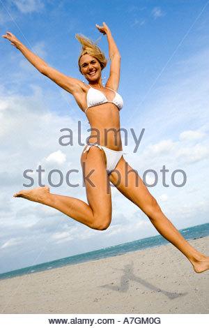 A woman in a bikini jumping on a beach - Stock Photo