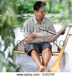 Young man sitting in a boat reading a newspaper - Stockfoto