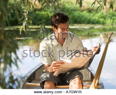 Young man sitting in a boat reading a newspaper - Stock Photo