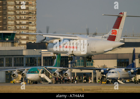 Scot Airways Dornier Do 328 110 landing at London City Airport and passengers boarding in the background 2004 - Stock Photo