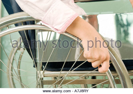 A woman sitting in a wheelchair - Stock Photo