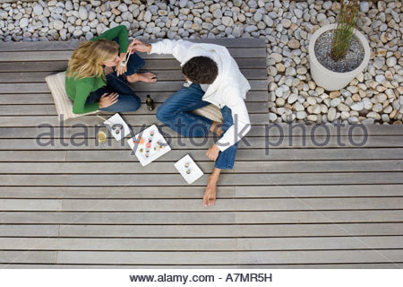 Couple sitting on patio decking eating sushi with chopsticks overhead view - Stock Photo