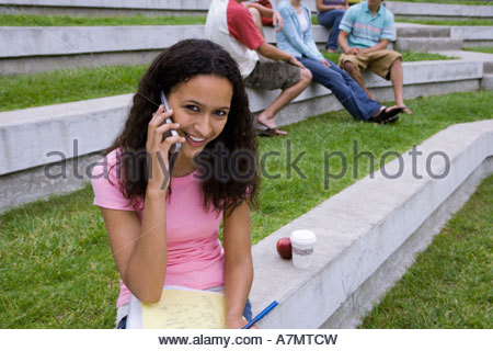 Teenage girl 17 19 sitting near friends study notes in lap using mobile phone smiling - Stock Photo