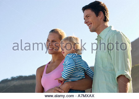 Two generation family standing on beach mother carrying daughter 2 3 smiling side view - Stockfoto