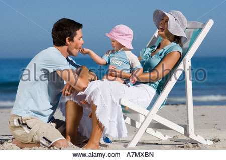 Family relaxing on beach girl 2 3 sitting in mother s lap feeding father laughing side view - Stockfoto