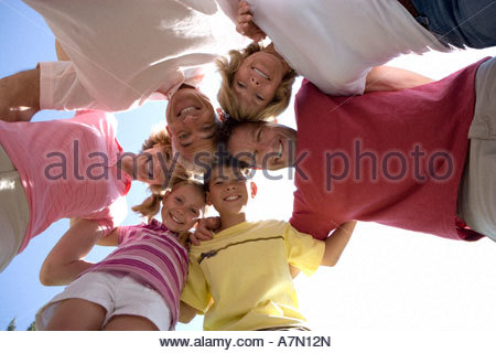 Three generation family standing in huddle smiling portrait upward view - Stock Photo
