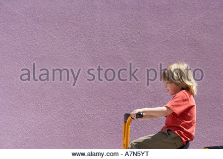 Blonde boy 4 6 riding on toy tricycle beside purple wall smiling profile - Stockfoto