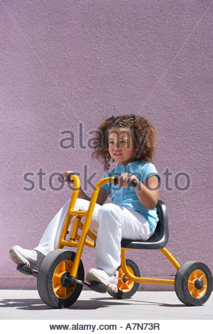Girl 4 6 riding on toy tricycle smiling side view - Stock Photo