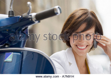 Woman sitting beside scooter using mobile phone smiling close up - Stock Photo