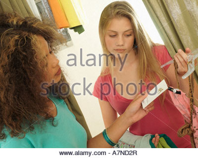 Two teenage girls 15 17 shopping in clothes shop checking price tag close up tilt - Stock Photo