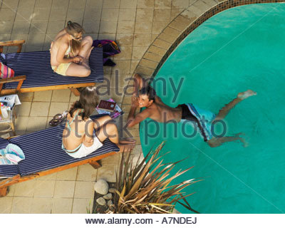 Two Teenage Girls Lounging In A Swimming Pool Stock Photo