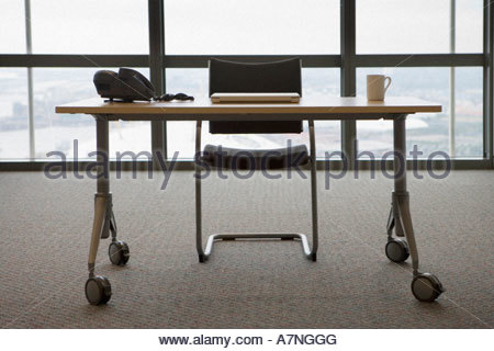 Desk and chair in office front view window in background - Stock Photo
