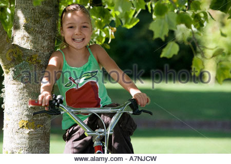 Girl 7 9 wearing green vest top with picture of apple sitting on bicycle in garden leaning against tree trunk smiling - Stock Photo