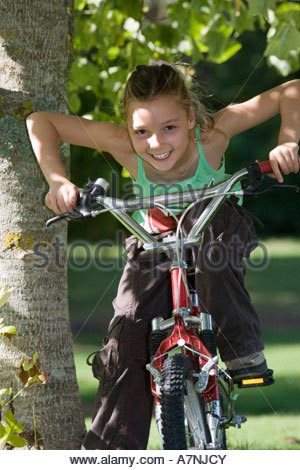 Girl 7 9 sitting on bicycle beside tree in garden leaning forwards smiling front view portrait - Stock Photo