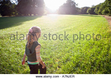 Blonde girl 7 9 walking in field in bright sunlight rear view trees in background lens flare - Stock Photo