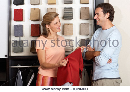 Couple standing beside fabric swatch display in shop, woman holding red textile sample, smiling - Stock Photo
