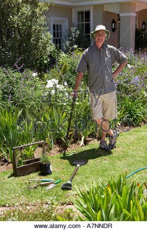 Senior man standing on lawn gardening leaning on garden fork hand on hip smiling portrait - Stock Photo