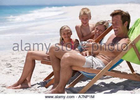 Family relaxing in deckchairs on beach father taking photograph with camera smiling side view - Stock Photo