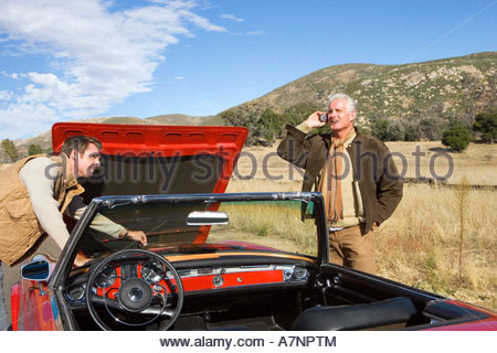 Father and son experiencing car trouble on country road man looking at engine senior man using mobile phone - Stock Photo