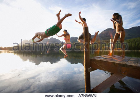 Four young adults diving from jetty into lake at sunset side view lens flare - Stock Photo