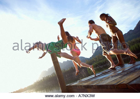 Four young adults diving from jetty into lake on sunny day rear view tilt - Stock Photo
