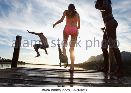 Four young adults in swimwear jumping from jetty into lake at sunset rear view surface level - Stock Photo