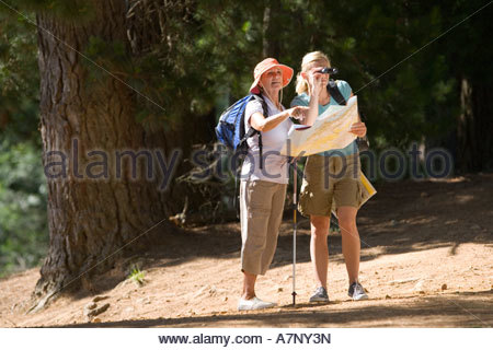 Senior woman and adult daughter hiking on woodland trail young woman looking through binoculars holding map - Stock Photo