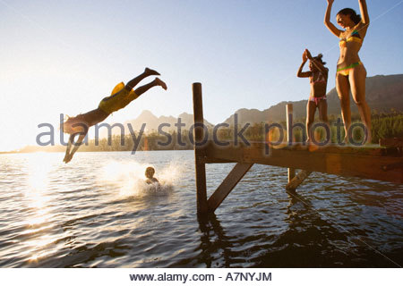 Father and son 8 10 in swimwear diving off jetty into lake at sunset mother and daughter 7 9 cheering lens flare - Stockfoto
