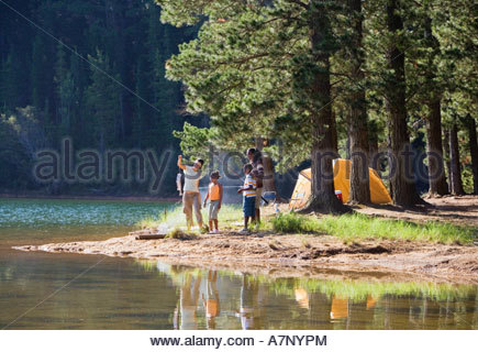 Family in mid distance fishing beside lake on camping trip woman holding catch man with fishing rod - Stock Photo