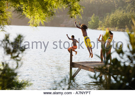 Father and son 8 10 in swimwear jumping off jetty into lake mother and daughter 7 9 cheering rear view - Stockfoto