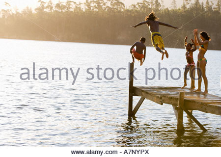 Father and son 8 10 in swimwear jumping off jetty into lake at sunset mother and daughter 7 9 cheering rear view - Stockfoto