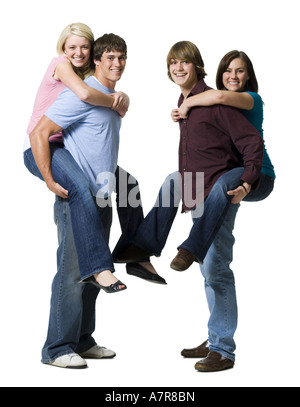 Two boys giving two girls piggy back rides - Stock Photo