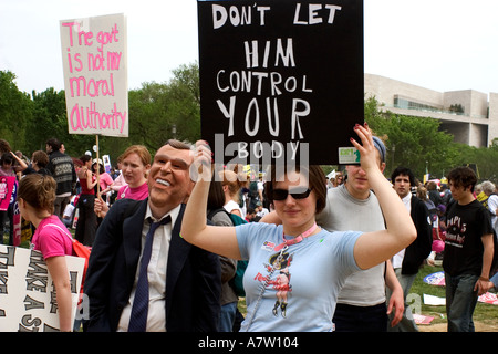 A woman holds sign as she stands next to somebody wearing George W Bush mask This was at the Pro Choice Rally on - Stock Photo