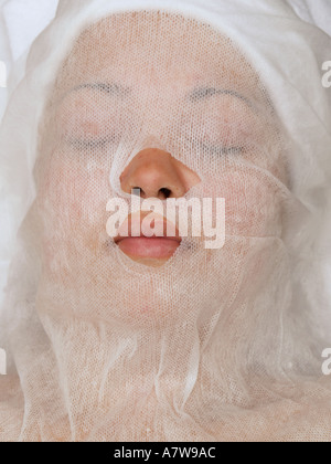 Womans face covered with white mesh for protection from a clay mask - Stock Photo