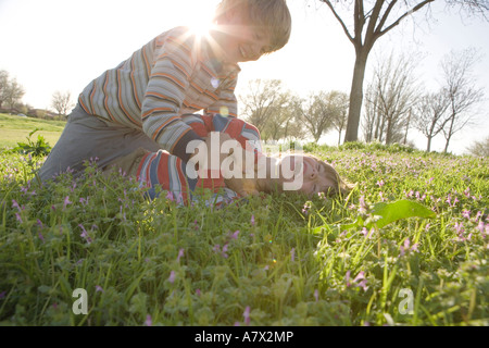 two boys playing in flower fields at sunset - Stockfoto