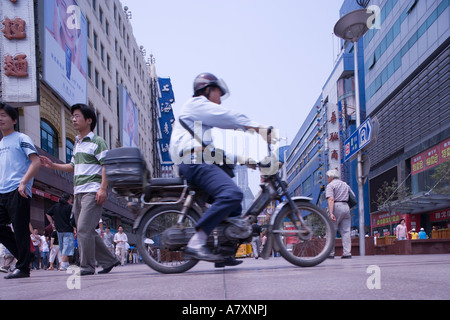 Asia, China, Shanghai, Pedestrians walking through retail shopping and restaurant district lining Nanjing Road on - Stock Photo