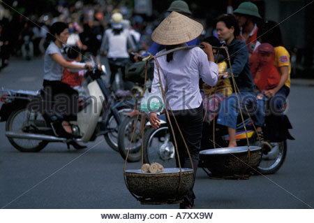 Asia, Vietnam, Hanoi, Woman carries traditional baskets through chaotic traffic in city's Old Quarter - Stock Photo