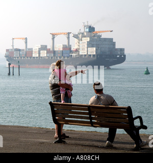 Men with a little girl ship watching on Southampton Water southern England UK The MAERSK Nottingham - Stock Photo