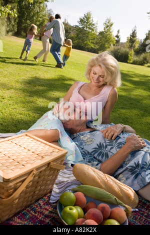 Grandparents and family in a park with a picnic - Stock Photo