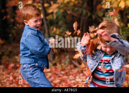 Young brothers exchange a playful toss of autumn leaves October in Blendon Woods Metro Park Columbus Ohio model - Stock Photo