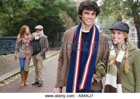 Four friends walking through park - Stock Photo