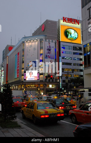 Traffic and Neon Lights on Ginza Shopping District in Tokyo Japan - Stock Photo