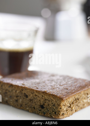 coffee cake slice on side plate with coffee maker and a shot of espresso in the background blurred - Stock Photo